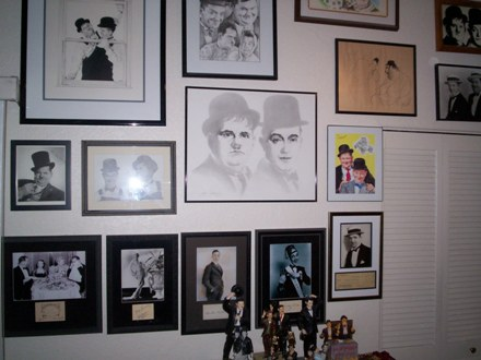 Various items on a living room wall – the bottom row includes framed photos, with signatures, of Laurel & Hardy, Thelma Todd, Buster Keaton, Charley Chase and, finally, a Stan Laurel check.