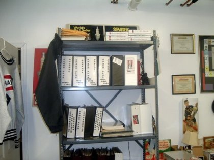 Book shelf with 3-ring binders of assorted spark plug literature.