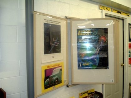 Poster rack displaying spark plug posters.