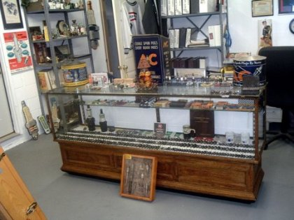 Antique glass display case displaying AC spark plugs and AC items.
