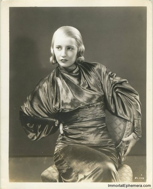 Barbara Stanwyck 1933 Press Photo in promotion of Baby Face - Lady in Scarlet Velvet: Barbara Stanwyck features this alluring negligee of scarlet velvet in her next Warner picture BABY FACE